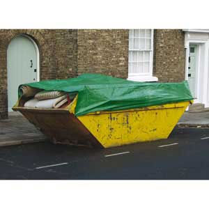Green tarpaulin in use to cover a skip