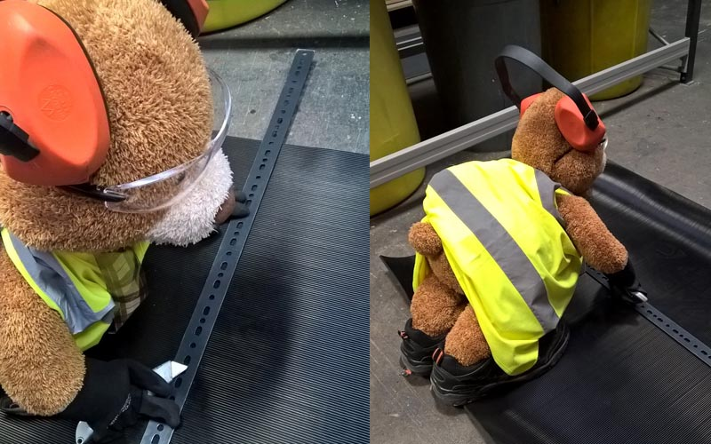 Health and Safety Bear carefully cutting the rubber matting