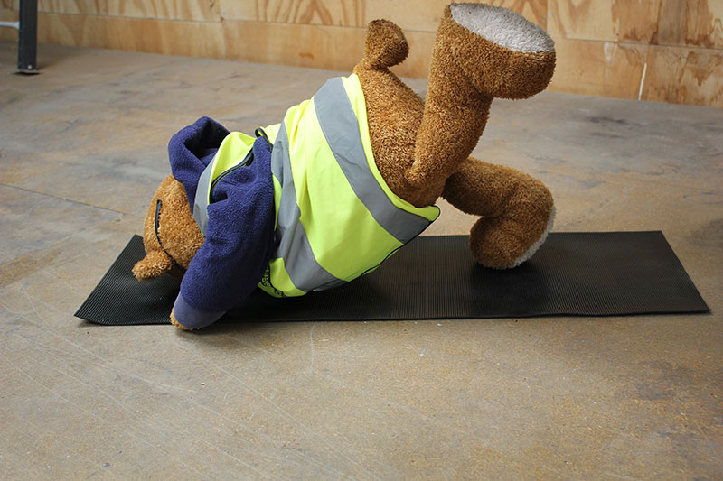 Health and Safety Bear demonstrates Leg High Yoga Pose