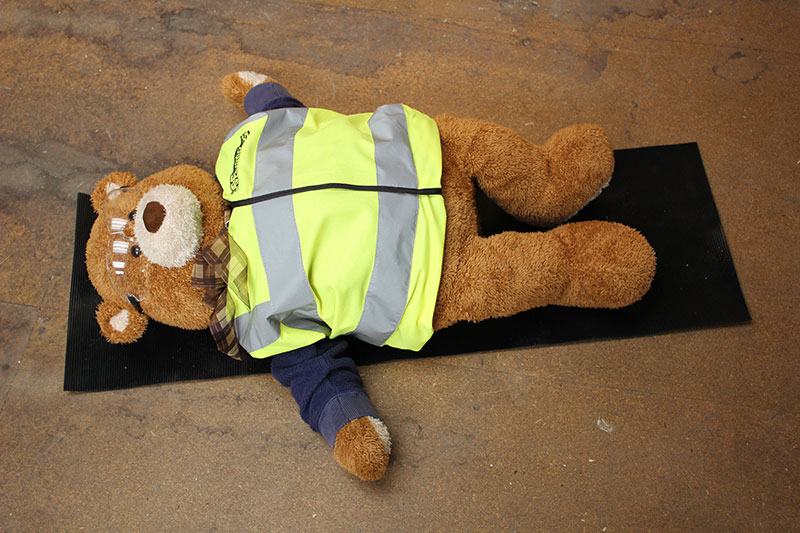 Health and Safety Bear demonstrates Shavasana Yoga Pose
