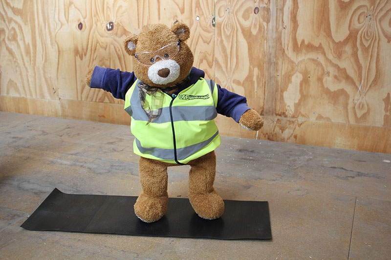 Health and Safety Bear demonstrates Warrior 2 Yoga Pose
