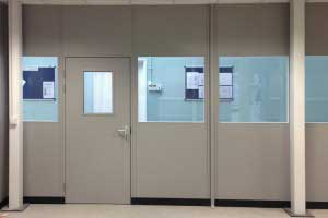 Part-glazed double skin steel partitioning with steel door
