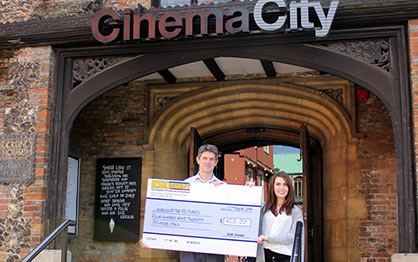 Mark Atkinson receives the cheque on behalf of Norfolk at the Pictures