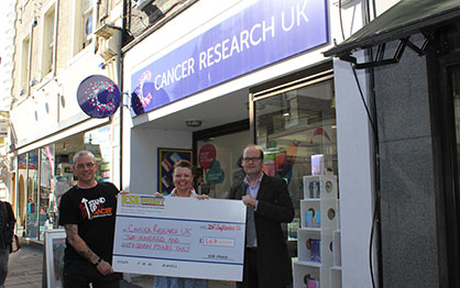 Martin Donovan and Martin Gilmour present the cheque to the manager of the Cancer Research Charity Shop, Norwich